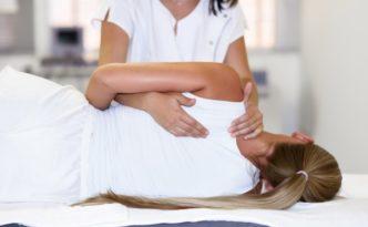 profesjonalny-fizjoterapeuta-zenski-masaz-ramion-do-kobiety-blondynka